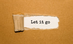 The text Let it go appearing behind torn brown paper